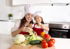 Happy mother and little daughter at home kitchen preparing salad in apron and cook hat Royalty Free Stock Photo