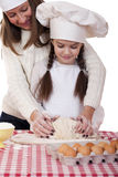 Happy mother with little daughter joyful cooking Stock Photos