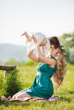 Happy mother with little daughter on the meadow Stock Photography