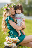 Happy mother with little daughter on the meadow Royalty Free Stock Photo
