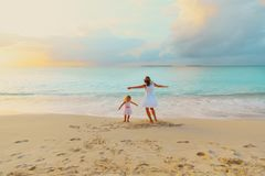 Happy mother with little daughter play on beach at sunset. Happy mother with little daughter play on tropical beach at sunset Stock Images