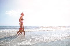 Happy mother and little daughter run on the beach at sunset. Summer vacation Stock Photography