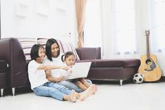 Happy mother and little daughter using a laptop computer. Happy mother and little daughter are sitting room on a floor at home and using a laptop computer Royalty Free Stock Images