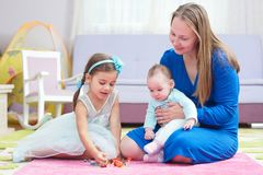 Happy Mother And Little Daughters Having Fun At Home Stock Photo