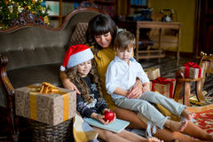 Happy mother, little girl and boy with gift box. Over living room and christmas tree background Royalty Free Stock Image