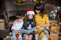 Happy mother, little girl and boy reading a book Stock Photography