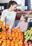 Happy mother and little girl choosing fresh fruits Stock Photos