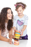 Happy mother and little girl with colorful donuts Royalty Free Stock Photo