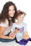 Happy mother and little girl with colorful donuts Royalty Free Stock Image