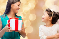 Happy mother and little girl with gift box. Christmas, holidays, celebration, family and people concept - happy mother and little girl with gift box over beige Stock Photo