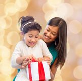 Happy mother and little girl with gift box. Christmas, holidays, celebration, family and people concept - happy mother and little girl with gift box over beige Royalty Free Stock Image