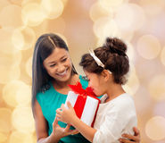 Happy mother and little girl with gift box. Christmas, holidays, celebration, family and people concept - happy mother and little girl with gift box over beige Royalty Free Stock Photo