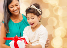 Happy mother and little girl with gift box. Christmas, holidays, celebration, family and people concept - happy mother and little girl with gift box over beige Royalty Free Stock Images