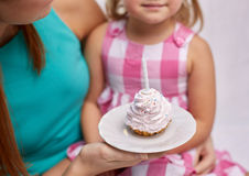 Happy mother and little girl holding cupcake Royalty Free Stock Photography