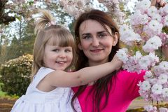 Happy Mother and Little Girl near blooming tree Stock Images