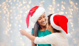 Happy mother and little girl in santa hats Royalty Free Stock Photography