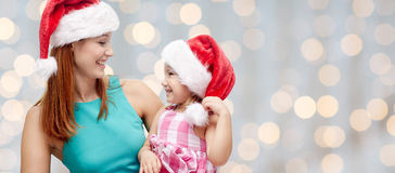 Happy mother and little girl in santa hats Stock Photos