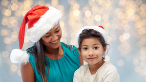 Happy mother and little girl in santa hats Royalty Free Stock Photo