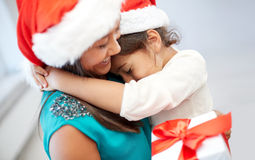 Happy mother and little girl in santa hats at home stock images