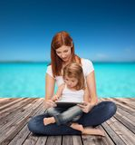 Happy mother with little girl and tablet pc Royalty Free Stock Images