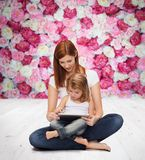 Happy mother with little girl and tablet pc Stock Photo