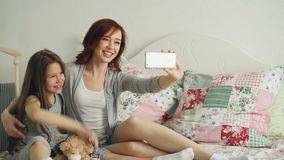 Happy mother and little girl taking selfie photo with smartphone camera and have fun grimacing while sitting in cozy bed. Room at home stock footage