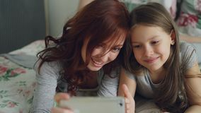 Happy mother and little girl taking selfie photo with smartphone camera and have fun grimacing while sitting in cozy bed. Room at home stock video footage