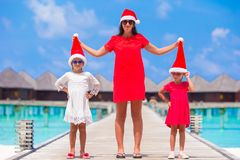 Happy mother and little girls in Santa hat near. Young mother and little girls in Santa hat at tropical beach Stock Photo