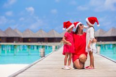 Happy mother and little girls in Santa hat near. Young mother and little girls in Santa hat at tropical beach Stock Image