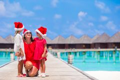 Happy mother and little girls in Santa hat near. Young mother and little girls in Santa hat at tropical beach Royalty Free Stock Photo