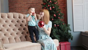 Happy mother and little son celebrate Christmas. Portrait of happy mother and adorable baby celebrate Christmas. New Year`s holidays. Toddler with mom in the stock video