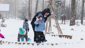 Happy mother and little son play, two children and man near they during snowfall in winter park stock video
