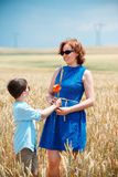 Happy mother with little son walking happily in wheat field Stock Image