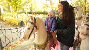 Happy Mother with Long Dark Hair and Little Daughter Riding on Carousel and Laughing Together. Baby Girl Wearing Purple. Jacket Sitting on a White Horse in a stock video footage