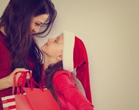 Happy mother looking on her cute daughter in santa clause hat and holding Christmas present packages stock photos