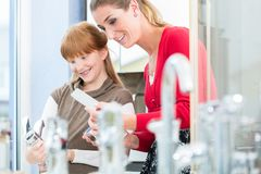 Happy mother looking with her daughter at two faucets. Portrait of a happy mother looking together with her daughter at two different bathroom faucets in a stock photos