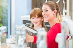Happy mother looking with her daughter at two faucets in a sanitary ware shop royalty free stock photo