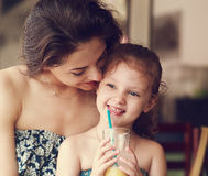 Happy mother looking and hugging her daughter who drinking citru Royalty Free Stock Photos
