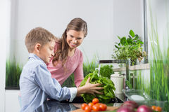 Happy mother looking at son washing vegetables in kitchen stock photography