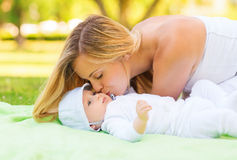 Happy mother lying with little baby on blanket Stock Image