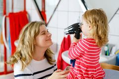 Happy mother making the hairs of cute little toddler girl with hair dryer. Adorable healthy baby child with wet hairs royalty free stock photos