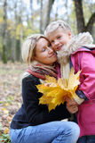 Happy mother with maple leaflets hugs her daughter. Happy mother with yellow maple leaflets hugs her daughter in autumn forest. Shallow depth of field. Focus on royalty free stock photography