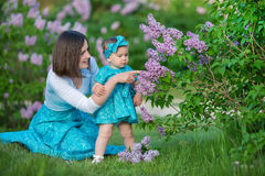 Happy mother mom with daughter enjoying time on a awesome place between lilac syringe bush.Young ladies with basket full of flower. S dressed in jeans and royalty free stock photography