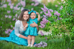 Happy mother mom with daughter enjoying time on a awesome place between lilac syringe bush.Young ladies with basket full of flower. S dressed in jeans and royalty free stock photo