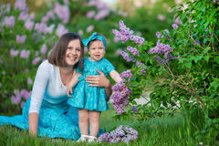 Happy mother mom with daughter enjoying time on a awesome place between lilac syringe bush.Young ladies with basket full of flower. S dressed in jeans and stock images