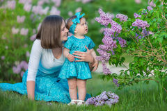 Happy mother mom with daughter enjoying time on a awesome place between lilac syringe bush.Young ladies with basket full of flower. S dressed in jeans and stock photography