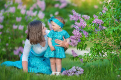 Happy mother mom with daughter enjoying time on a awesome place between lilac syringe bush.Young ladies with basket full of flower. S dressed in jeans and stock image