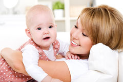 Happy mother with newborn baby. Portrait of young happy mother with newborn baby at home Royalty Free Stock Images