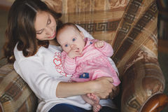 Happy mother with newborn baby girl in her arms. Stock Image