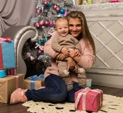 Happy mother with newborn son, sitting on a floor near a Christmas tree. Waiting for a holiday. Royalty Free Stock Images